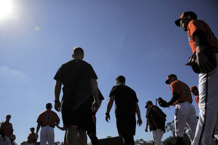 Orioles infielder Ivan De Jesus Jr. (right) and the team head onto the practice field during the first official day of workouts with the full squad. (Karl Merton Ferron/Baltimore Sun)