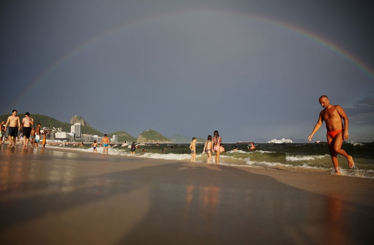 People gather on Copacabana Beach in front of a partial rainbow during New Year's Eve celebrations on Dec. 31, 2013 in Rio de Janeiro, Brazil. (Mario Tama/Getty Images)