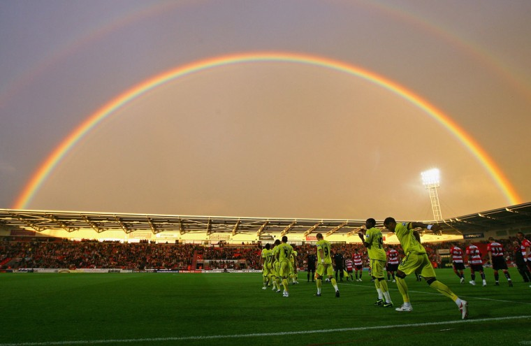 Tottenham Hotspur and Doncaster Rovers players run on to the pitch as a rainbow arcs over Keepmoat Stadium before the Carling Cup second round match between Doncaster Rovers and Tottenham Hotspur on Aug. 26, 2009 in Doncaster, England. (Alex Livesey/Getty Images)