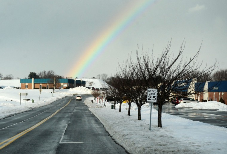 A rainbow adds a dash of color to a drab sky over the landscape of the Forest Hill Industrial Park as the sun pops back through the clouds after a brief but heavy rain Feb. 18, 2014. (Baltimore Sun Media Group)