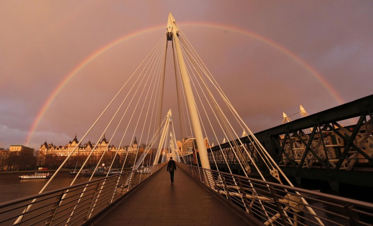 A rainbow appears as a pedestrian crosses one of the Golden Jubilee Bridges in London Jan. 31, 2014. (Suzanne Plunkett/Reuters)