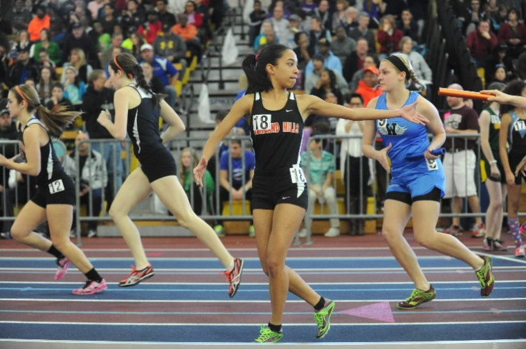Oakland Mills' Oriana Ovideo reaches back for the baton as she begin the anchor leg of the 2A girls 4x800 meter relay during the 1A/2A indoor track state championships at the Prince George's Sports and Learning Complex in Landover on Monday, Feb. 17. (Brian Krista/BSMG)