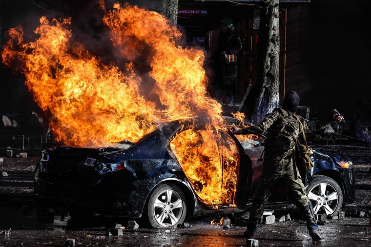 Anti-government demonstrators burn a car during violent clashes with riot police and soldiers in Kiev, Ukraine, on Tuesday, Feb. 18, 2014. (Yevgeny Maloletka/Itar-Tass/Zuma Press/MCT)