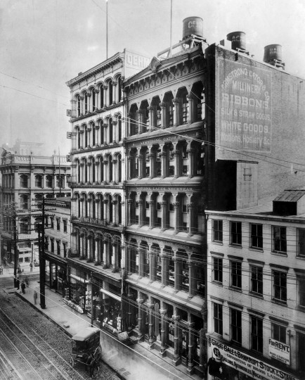 "The airy glisten of iron fronts, as shown here in some vanished specimens from the corner of Charles and Baltimore streets, still decorate parts of lower Manhattan and some West Coast ports, and are newly stylish. But of about 1,500 Baltimore structures of this type estimated to be standing in 1904, we have probably fewer than a dozen heavily re-modeled survivors today. These are the fabled ""iron fronts"" that blossomed just before the civil war. The 1851 Sun Iron building, a pioneering iron-front venture in its day, was featured on the cover of sheet music and widely admired, but melted in the 1904 fire along with dozens of its iron-front neighbors. By the 1970s, high-ceilinged loft living and flow-through rooms with natural lighting were back in style- but it was too late."