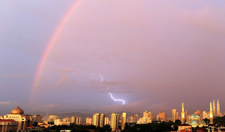 A rainbow and lightning come together as the sun casts shadows on the buildings in Kuala Lumpur on July 1, 2010. (Saeed Khan/AFP/Getty Images)