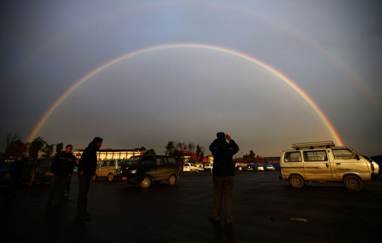 A Nepalese man takes a photo of a rainbow with his mobile phone as it stretches over the horizon near the Kathmandu Domestic airport in Kathmandu on Feb.16, 2014. (AFP/Getty Images)