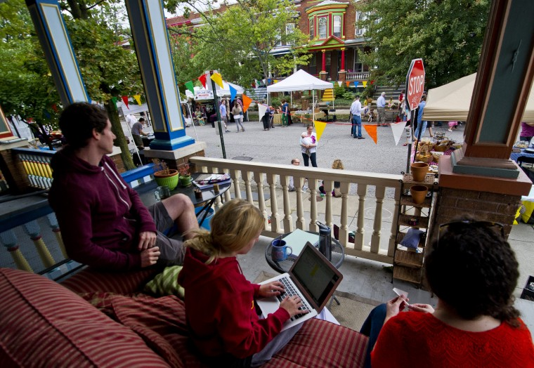 Alex Rongione (from left), Jessica Spomer and Emma Glinsmann watch the festivities of the Abell Community Street Fair from their front porch in Baltimore City on September 22, 2013. The event, sponsored by the Abell Improvement Association, is the community's biggest fundraiser and a way to celebrate what makes the 9-square block community unique. (Scott Serio/Baltimore Sun/Sept. 22, 2013)