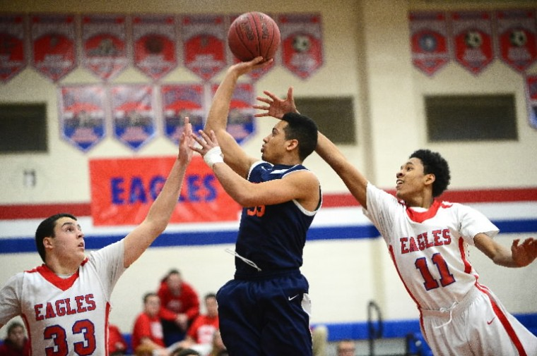 Reservoir's Seth Henry, center, puts up a shot over Centennial's Tom Brown, left, and Isaiah White. (Matt Hazlett/BSMG)