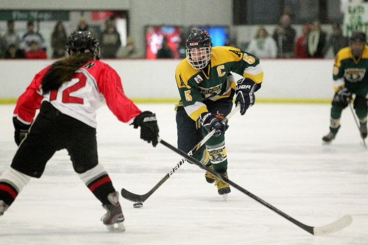 Glenelg's Karen Hudson, left, defends Atholton's Matt Haney during the annual County Cup ice hockey game at the Columbia Ice Rink. (Jen Rynda/BSMG)