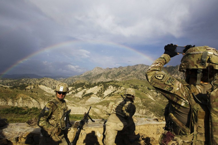 A paratrooper from Chosen Company of the 3rd Battalion (Airborne), 509th Infantry photographs a rainbow toward the end of a helicopter assault mission near the town of Ahmad Khel in Afghanistan's Paktiya Province July 16, 2012. (Lucas Jackson/Reuters)