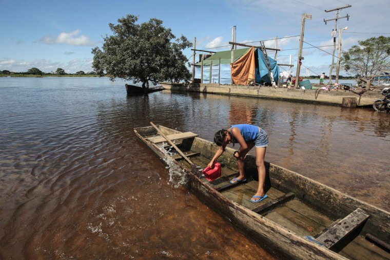 A girl removes water from a boat in the flood in Puerto Varador in Trinidad in the northeast region in Beni department in Bolivia, February 28, 2014. Floodwaters from near record rainfall have flooded large parts of northeast Bolivia and northwest Brazil, according to government sources in both countries. (REUTERS/David Mercado)