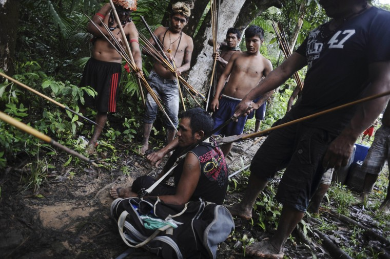 Munduruku Indian warriors stand guard over an illegal gold miner who was detained by a group of warriors searching out illegal gold mines and miners in their territory near the Caburua river, a tributary of the Tapajos and Amazon rivers in western Para state January 20, 2014. The Munduruku tribe has seen their land encroached on by wildcat miners in search of gold, and the tribe's leaders travelled to the capital Brasilia last year to demand the federal government remove non-indigenous miners from their territory. Rather than wait for a court decision to start the process - which could take years - the Munduruku decided to take matters into their own hands and expel the wildcat miners. Picture taken January 20, 2014. (Lunae Parracho/Reuters)