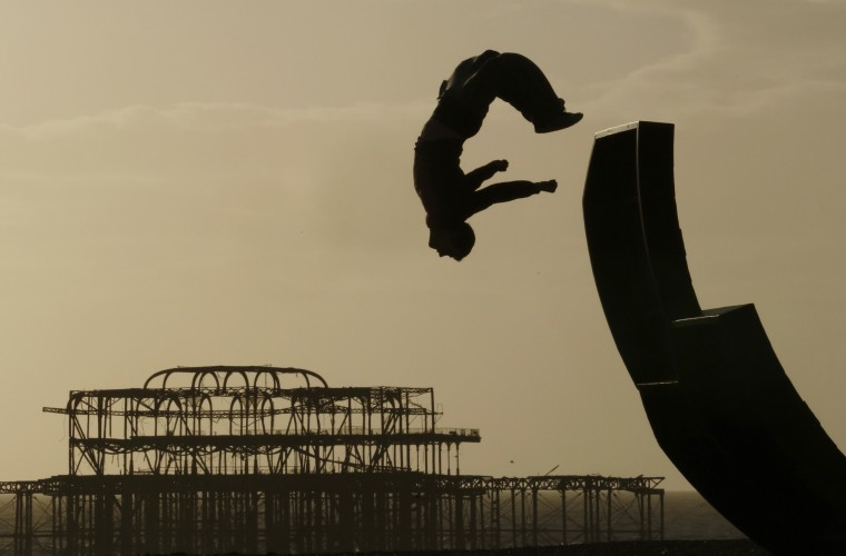 A man somersaults off a sculpture on the beach in front of the old West Pier in Brighton February 26, 2014. (REUTERS/Luke MacGregor)