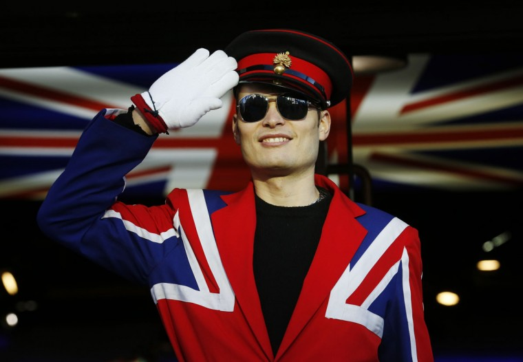 A doorman dressed in a Union flag jacket greets customers at a shop in Piccadilly Circus, London February 1, 2014. REUTERS/Luke MacGregor