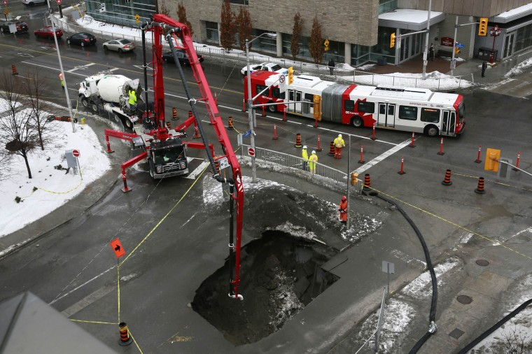 A view of a sinkhole opened up at the intersection of Laurier Avenue E and Waller Street, near the University of Ottawa, in Ottawa February 21, 2014. The sinkhole is about eight meters (26 feet) wide and 12 meters (39 feet) deep. (REUTERS/Blair Gable)