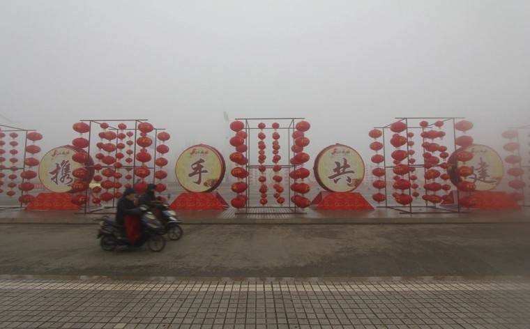 Residents ride their electric bicycles past Chinese New Year decorations near a street on a hazy day in Binzhou, Shandong province February 1, 2014. China's meteorological authority issued a yellow alert for foggy weather on Friday as heavy fog will continue to shroud central and eastern China, Xinhua News Agency reported. REUTERS/Stringer