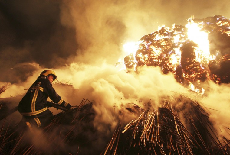 A firefighter attempts to extinguish a fire which broke out on piles of reed at a paper factory in Changde, Hunan province February 16, 2014. No casualty was reported, according to local media. Picture taken February 16, 2014. (Stringer/Reuters)