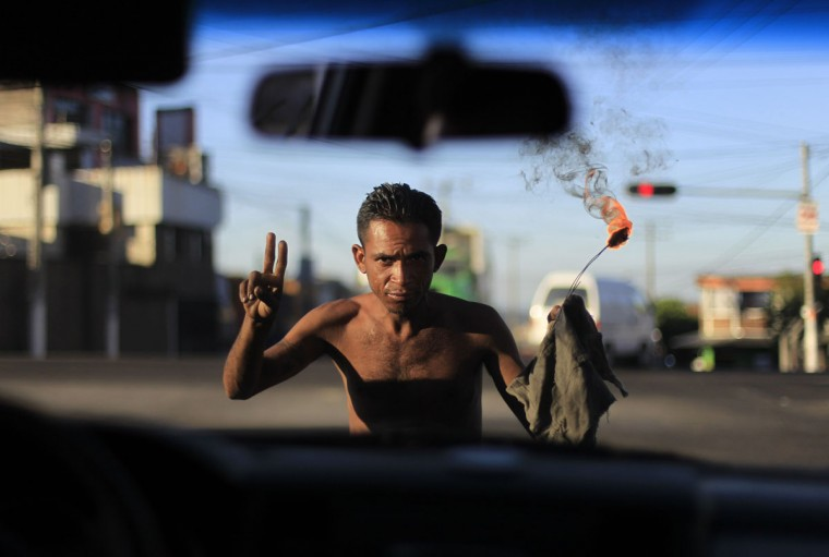 A street performer gestures in front of a car on a street in San Salvador January 10, 2014. Former guerrilla commander Vice President Salvador Sanchez Ceren hopes to keep his left-wing party Farabundo Marti National Liberation Front (FMLN) in power in El Salvador's presidential election on February 2, but he faces a strong challenge from right-wing rival Norman Quijano of the conservative Nationalist Republican Alliance (Arena) party, who wants to use the army to battle powerful street gangs. Picture taken January 10, 2014. REUTERS/Ulises Rodriguez