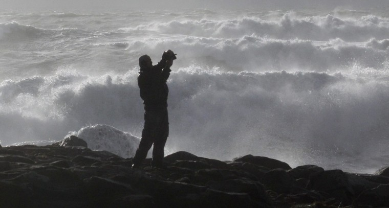 A man photographs waves breaking on the Brittany coast at Penmarch in Finistere during high winds and an unusually high tide coefficient, February 1, 2014. REUTERS/Mal Langsdon