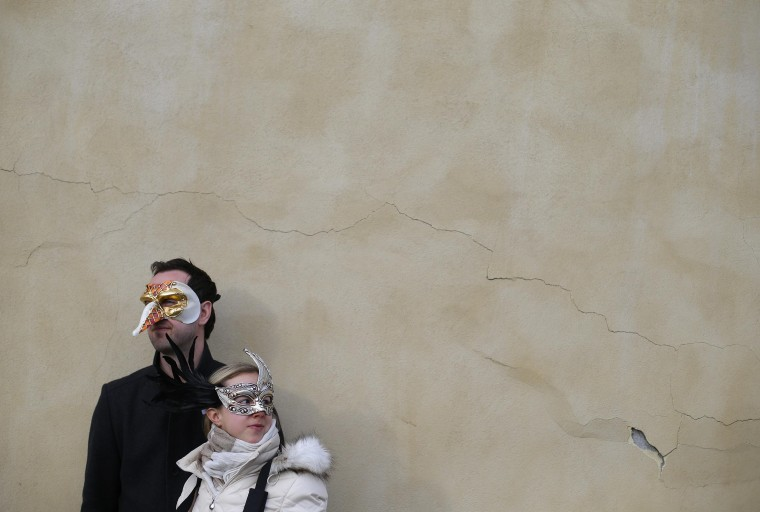 "A couple watches a ""Zombie Walk"", part of the Venetian Carnival, in Venice February 15, 2014. REUTERS/Max Rossi"