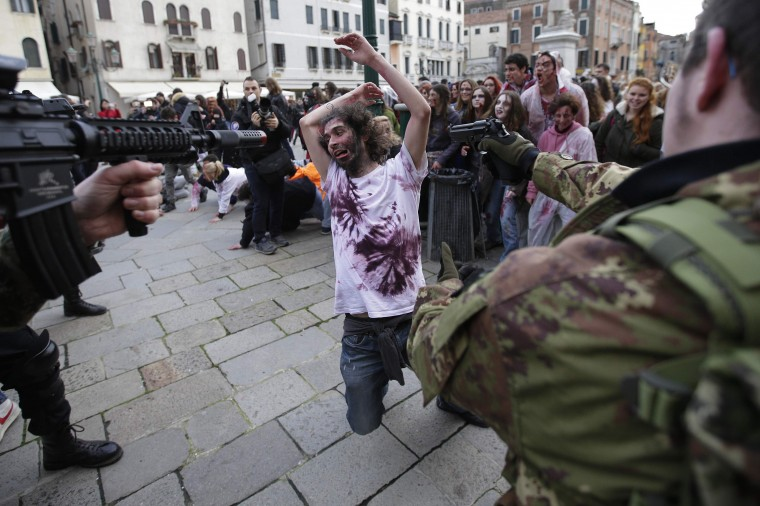 """Participants dressed as zombies and soldiers simulate a fight during a """"Zombie Walk"""", part of the Venetian Carnival, in Venice February 15, 2014. REUTERS/Max Rossi"""
