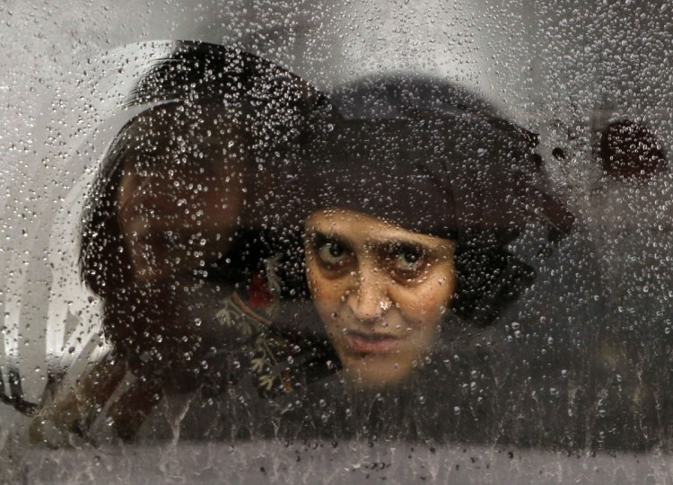 A Kashmiri Muslim woman looks through the window of a car at a police checkpoint during restrictions as it rains in Srinagar February 11, 2014. Authorities imposed restrictions in parts of Srinagar city on Tuesday during the third day of a strike called by separatists to demand for the remains of Mohammad Maqbool Bhat and Mohammad Afzal Guru. Bhat, founder and leader of JKLF, was hanged and buried in an Indian jail on February 11, 1984 on charges of killing an Indian intelligence officer. Guru, a Kashmiri man, was executed on February 9, 2013, for an attack on India's parliament in 2001. (Danish Ismail/Reuters)