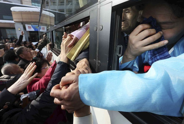 South Koreans hold hands with their North Korean family members (in bus) as they bid farewell after their three-day temporary family reunion at the Mount Kumgang resort in North Korea, February 25, 2014.The six days of family reunions take place under the cloud of a U.N. report on human rights abuses in North Korea, which investigators have said were comparable to Nazi-era atrocities. A group of South Koreans crossed the world's most heavily fortified border on Sunday, a frontier that separates two countries that remain at war after their conflict ended in an armistice rather than a peace treaty. (Lee Ji-eun/Yonhap/Reuters)