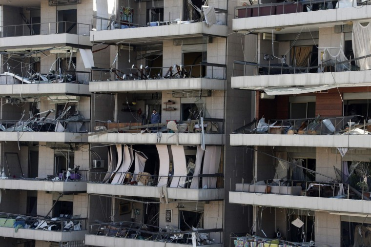 A man stands at the balcony of a damaged building at the site of an explosion in the southern suburbs of Beirut.The al Qaeda-linked Abdullah Azzam Brigades claimed a twin bomb attack in Beirut on Wednesday, saying such attacks would continue until Hezbollah forces withdrew from the fighting in Syria and its own fighters were released from Lebanese jails. (Mohamed Azakir/Reuters)