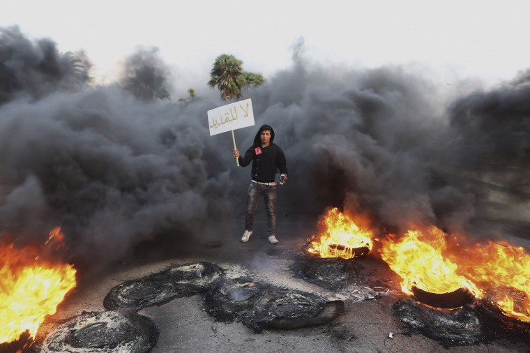"A man holds a sign which reads, ""Not extendable"" amid smoke and fire after angry protesters set tyres on fire in a street during a demonstration against the General National Congress (GNC) in Benghazi February 21, 2014. (REUTERS/Esam Omran Al-Fetori)"
