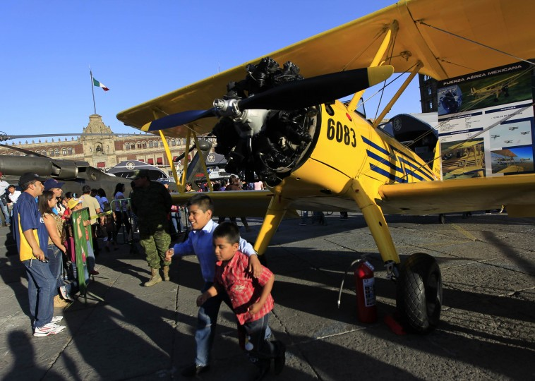 """Biplanes on the Zocalo: Children walk past a PT-17 Stearman airplane during the """"Armed Forces, Passion to Serve Mexico"""" army exhibition at Zocalo Square in downtown Mexico City on February 9, 2014. According to local media, the exhibition opened on February 8 and will remain until March 9. The National Palace is pictured in the background. (REUTERS/Henry Romero)"""