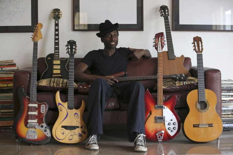 """Nigerian musician Keziah Jones sits on a sofa between guitars during an interview with Reuters at his home in Lagos February 25, 2014. A new superhero is fighting for freedom, justice and the Nigerian way in the mean streets of Lagos. And - oh, yes - he can dance too. Meet Captain Rugged, the creation of Nigerian musician Keziah Jones. He is the inspiration for Jones's latest """"blufunk"""" album release and, unusually, the subject of a graphic novel published along with it. The idea, Jones says, is to show off Nigeria's premier city to the outside world - as a place that is as arresting as Paris or London, yet also transformed by unshared oil wealth into a blight of shanty towns and homelessness. Picture taken February 25, 2014. (REUTERS/Akintunde Akinleye)"""