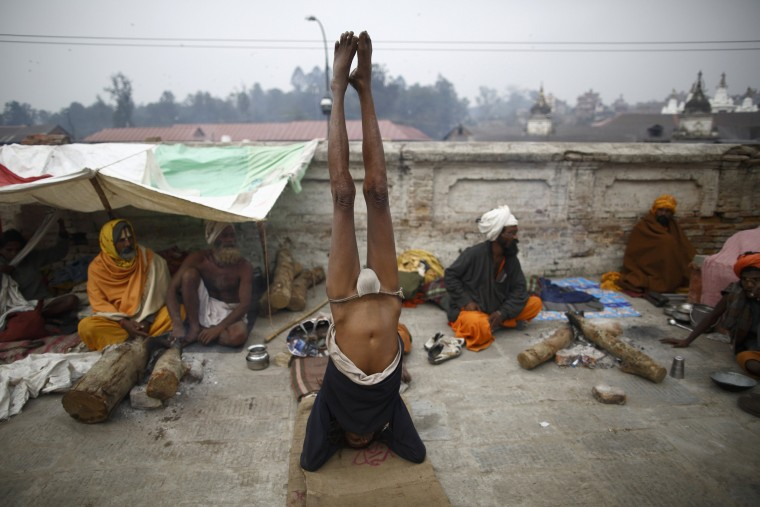 A Hindu holy man, or sadhu, performs yoga at the premises of Pashupatinath Temple in Kathmandu February 26, 2014. Hindu holy men from Nepal and India come to this temple to take part in the Shivaratri festival, which this year falls on February 27. Celebrated by Hindu devotees all over the world, Shivaratri is dedicated to Lord Shiva, and holy men mark the occasion by praying, smoking marijuana or smearing their bodies with ashes. (REUTERS/Navesh Chitrakar)