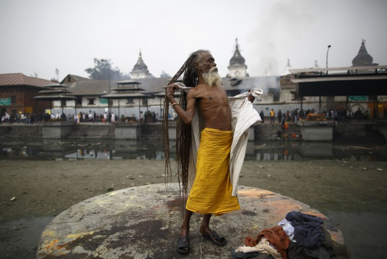 A Hindu holy man, or sadhu, changes after taking a bath at the bank of Bagmati River flowing through the Pashupatinath Temple in Kathmandu February 26, 2014. Hindu holy men from Nepal and India come to this temple to take part in the Shivaratri festival, which this year falls on February 27. Celebrated by Hindu devotees all over the world, Shivaratri is dedicated to Lord Shiva, and holy men mark the occasion by praying, smoking marijuana or smearing their bodies with ashes. (REUTERS/Navesh Chitrakar)