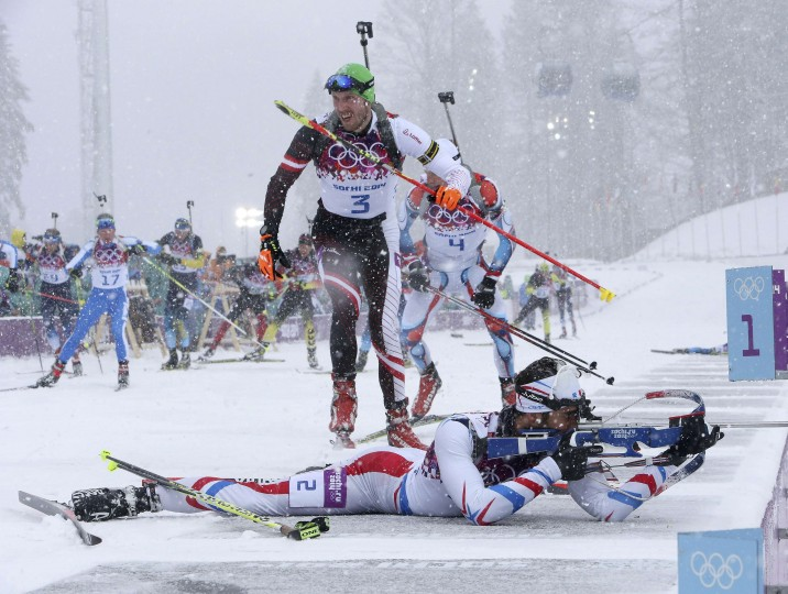 France's Martin Fourcade (bottom) shoots as Austria's Dominik Landertinger (C) leaves the shooting range during the men's biathlon 15km mass start event at the Sochi 2014 Winter Olympics in Rosa Khutor February 18, 2014. REUTERS/Sergei Karpukhin
