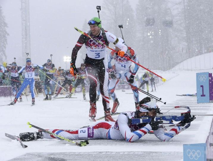 France's Martin Fourcade (bottom) shoots as Austria's Dominik Landertinger (C) leaves the shooting range during the men's biathlon 15km mass start event at the Sochi 2014 Winter Olympics in Rosa Khutor February 18, 2014. REUTERS/Sergei Karpukhin