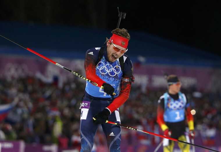 Russia's Anton Shipulin (L) celebrates after crossing the finish line ahead of Germany's Simon Schempp during the men's biathlon 4 x 7.5 km relay at the Sochi 2014 Winter Olympic Games in Rosa Khutor February 22, 2014. (REUTERS/Carlos Barria)