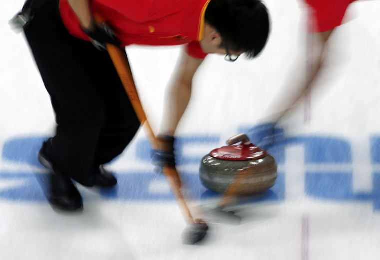China's Xu Xiaoming sweeps ahead of a stone during their men's curling round robin game against Britain at the Ice Cube Curling Center during the 2014 Sochi Winter Olympics February 17, 2014. (Marko Djurica/Reuters)
