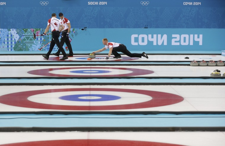 Canada's skip Brad Jacobs (right) delivers a stone as E. J. Harnden (L) and Ryan Harnden walk ahead of him to sweep during their men's curling round-robin game against Germany at the 2014 Sochi Olympics, February 10, 2014. (Mark Blinch/Reuters)