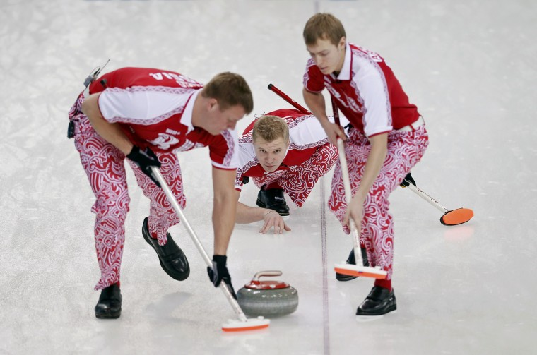 Russia's skip Alexey Stukalskiy (center) delivers a stone as Russia's Peter Dron (left) and Evgeny Arkhipov sweep during their men's curling round-robin game against Britain at the 2014 Sochi Olympics, February 10, 2014. (Mark Blinch/Reuters)