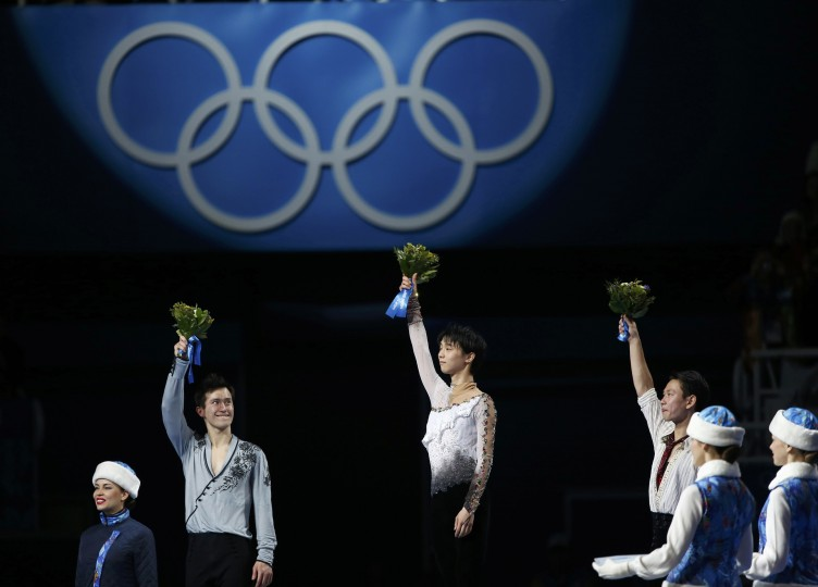 First-placed Japan's Yuzuru Hanyu (C), second-placed Canada's Patrick Chan (L) and third-placed Kazakhstan's Denis Ten celebrate on the podium after the figure skating men's free skating program at the Sochi 2014 Winter Olympics, February 14, 2014. REUTERS/Lucy Nicholson