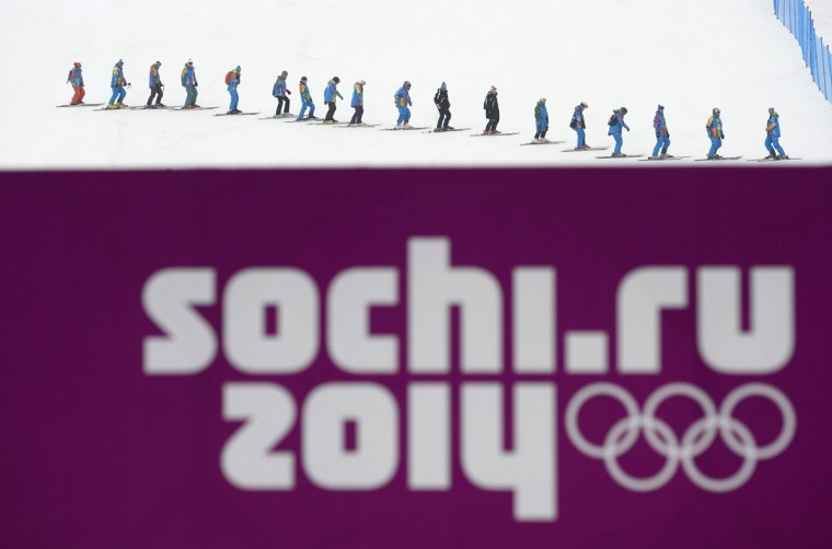 Workers clear the track next to the snowboard cross course during the 2014 Sochi Winter Olympic Games in Rosa Khutor February 17, 2014. (Dylan Martinez/Reuters)