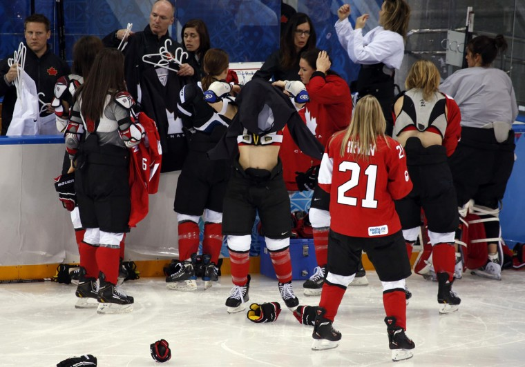 Players from the Canadian national ice hockey women's team change jerseys after gathering for a team photo before a training session at the Shayba Arena in preparation for the 2014 Sochi Winter Olympics. (REUTERS/Grigory Dukor)