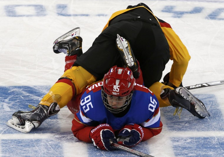 Germany's Sophie Kratzer, top, falls on Russia's Yelena Dergachyova during the second period of their women's ice hockey game at the 2014 Sochi Winter Olympics, February 9, 2014. (Grigory Dukor/Reuters)