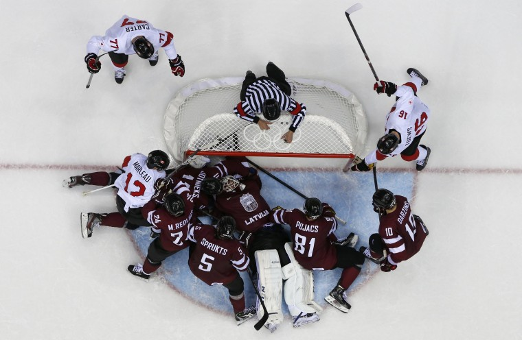 Latvia's goalie Kristers Gudlevskis (C) and Latvia's Kristaps Sotnieks (hidden) combine to make a goal line save from Canada's Patrick Marleau (L) in the third period of their men's quarter-finals ice hockey game at the 2014 Sochi Winter Olympic Games, February 19, 2014. (REUTERS/Gary Hershorn)