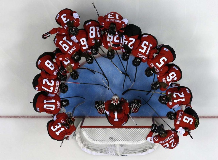 Canada's women's ice hockey team surrounds goalie Shannon Szabados before their women's ice hockey game against Finland at the 2014 Sochi Winter Olympics, February 10, 2014. (Mark Blinch/Reuters)