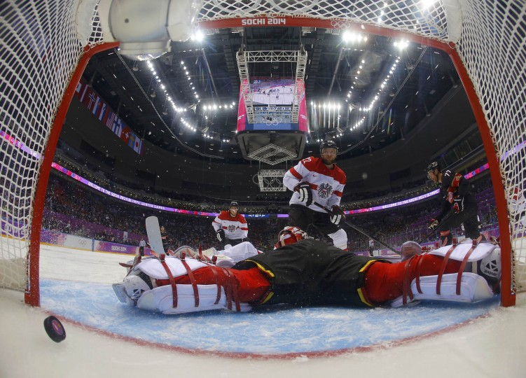Canada's Jeff Carter (R) scores his second goal on Austria's goalie Bernhard Starkbaum during the second period of their men's preliminary round ice hockey game at the 2014 Sochi Winter Olympic Games, February 14, 2014. REUTERS/Mark Blinch/Pool