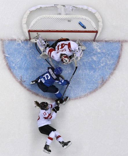Finland's Jenni Hiirikoski (6) scores the game winning goal in overtime on Switzerland's goalie Florence Schelling (41) as Switzerland's Sara Benz falls during their women's preliminary round hockey game at the Sochi 2014 Winter Olympic Games February 12, 2014. REUTERS/Brian Snyder