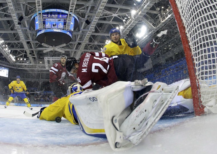 Sweden's goalie Henrik Lundqvist (L) battles with Latvia's Mikelis Redlihs during their men's preliminary round ice hockey game at the Sochi 2014 Winter Olympic Games February 15, 2014. REUTERS/Brian Snyder