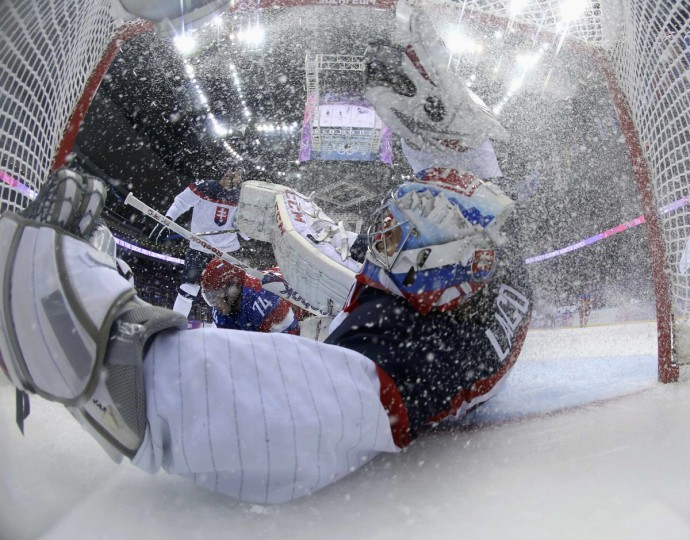 Slovakia's goalie Jan Laco (right) falls into the net after being hit by Russia's Alexei Yemelin during the second period of their men's preliminary round ice hockey game at the Sochi 2014 Winter Olympic Games February 16, 2014. (Bruce Bennett/Pool/Reuters)
