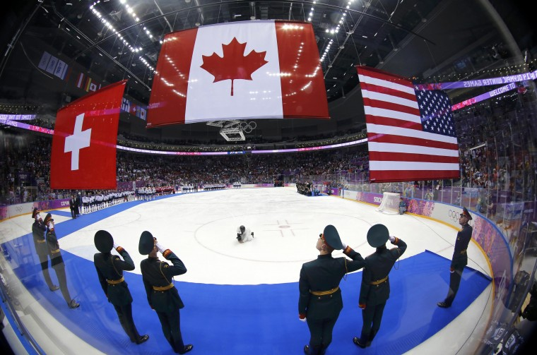 The flags of Canada, the United States and Switzerland (L) are raised after the women's ice hockey gold medal game at the Sochi 2014 Winter Olympic Games February 20, 2014. Canada won their fourth consecutive Olympic women's ice hockey gold medal with a wild 3-2 overtime win over the United States at the Sochi Games on Thursday. Switzerland beat Sweden earlier on Thursday to claim the bronze. (REUTERS/Mark Blinch)